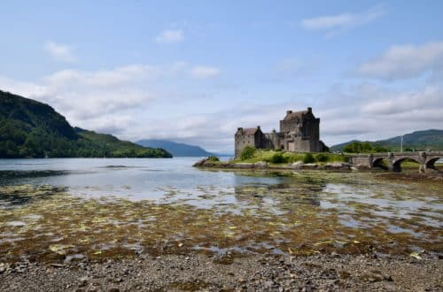 a rocky shore next to a body of water with a castle in the background
